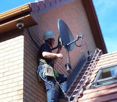 Warren Benskin on rooftop installing satellite dish